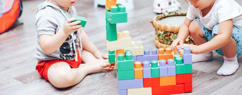 rapaz pequeno e menina que jogam brinquedos em casa fotos de stock