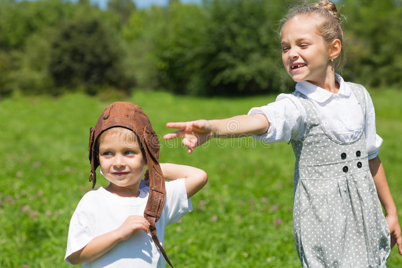 Rapaz pequeno e menina que jogam no parque foto de stock royalty free