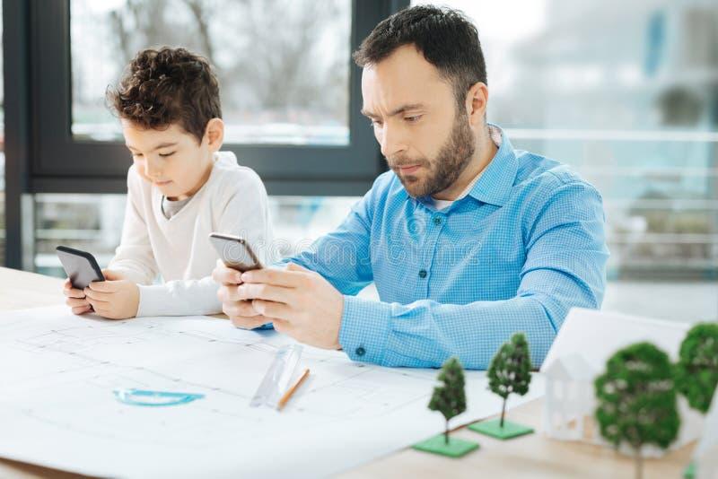 Rapaz pequeno e seu pai que estão sendo colados a seus telefones fotos de stock royalty free