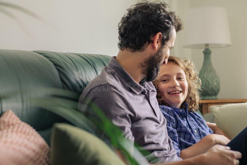 Rapaz pequeno e seu pai que falam junto em seu sofá imagem de stock royalty free