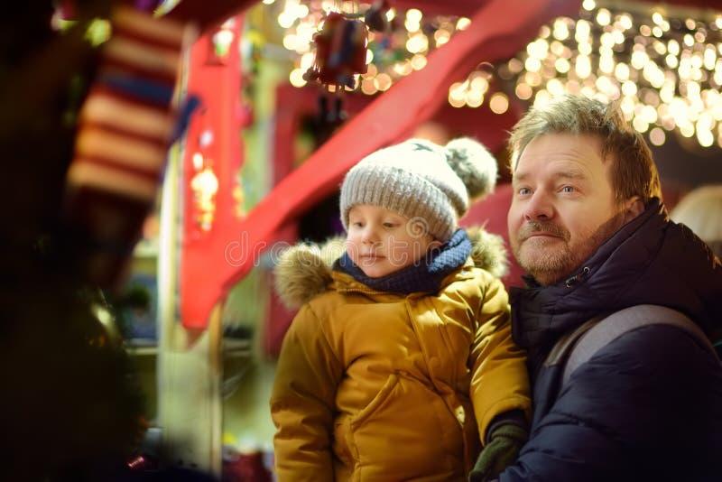 Rapaz pequeno e seu pai que têm o tempo maravilhoso no mercado do Xmas imagens de stock
