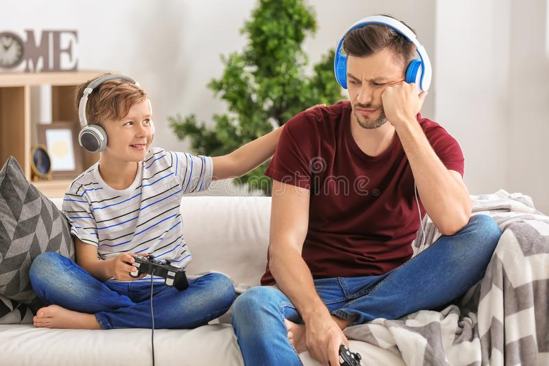 Rapaz pequeno e seu paizinho que jogam o jogo de vídeo junto em casa fotos de stock