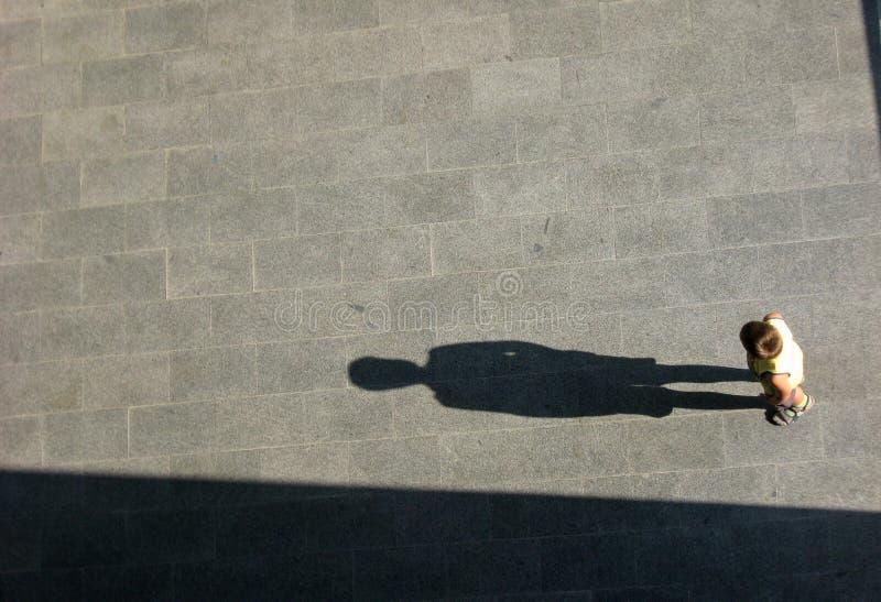 Rapaz pequeno e sombra grande imagem de stock