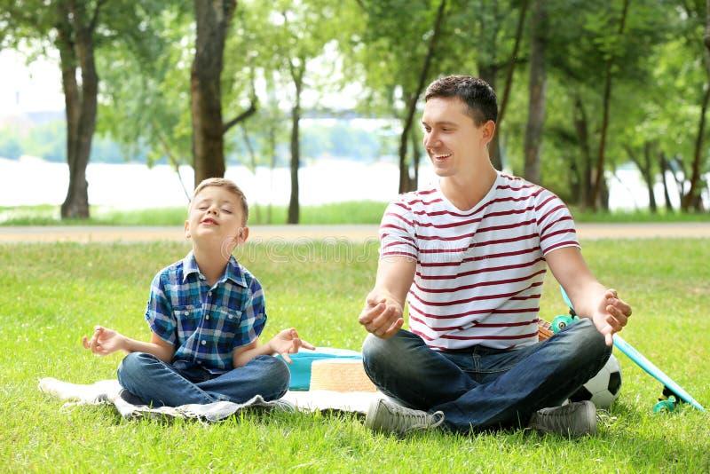 Rapaz pequeno e sua ioga praticando do pai fora foto de stock