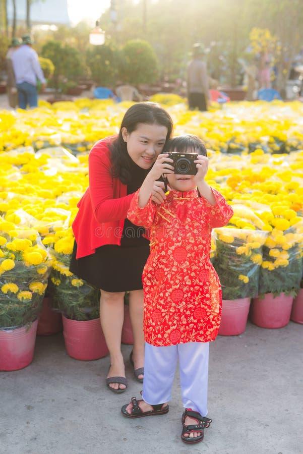 Rapaz pequeno e sua mãe nova bonita que tomam a imagem com a câmera digital da foto Família feliz que faz a foto na flor de Tet imagem de stock royalty free