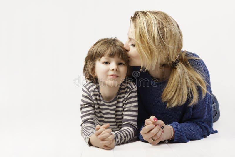 Rapaz pequeno e sua mãe que encontram-se para baixo, mãe que beija seu filho, outro no fundo branco imagens de stock royalty free