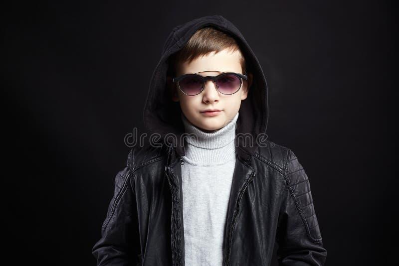 Rapaz pequeno elegante no hoodie e nos ?culos de sol fotografia de stock