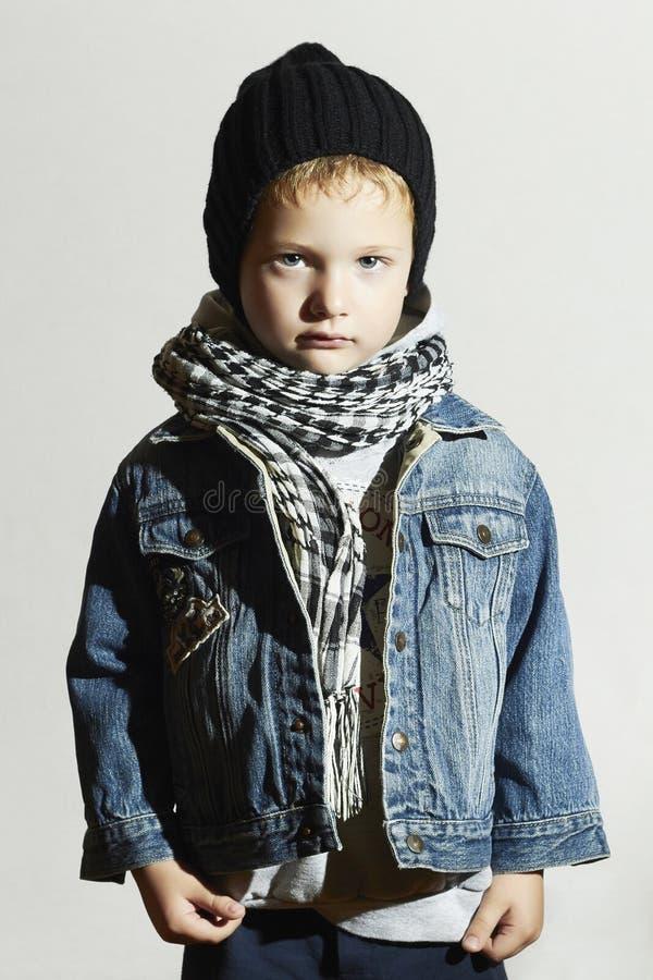 Rapaz pequeno elegante no lenço e nas calças de brim Estilo do inverno Miúdos da forma criança no tampão preto fotografia de stock royalty free