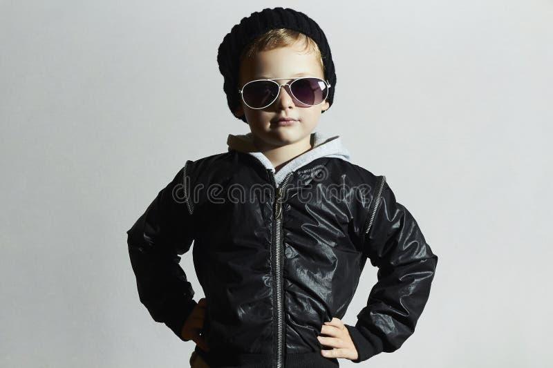 Rapaz pequeno elegante nos óculos de sol criança no tampão preto Estilo do inverno forma dos miúdos imagem de stock
