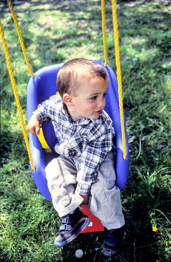 Rapaz pequeno em um balanço foto de stock royalty free