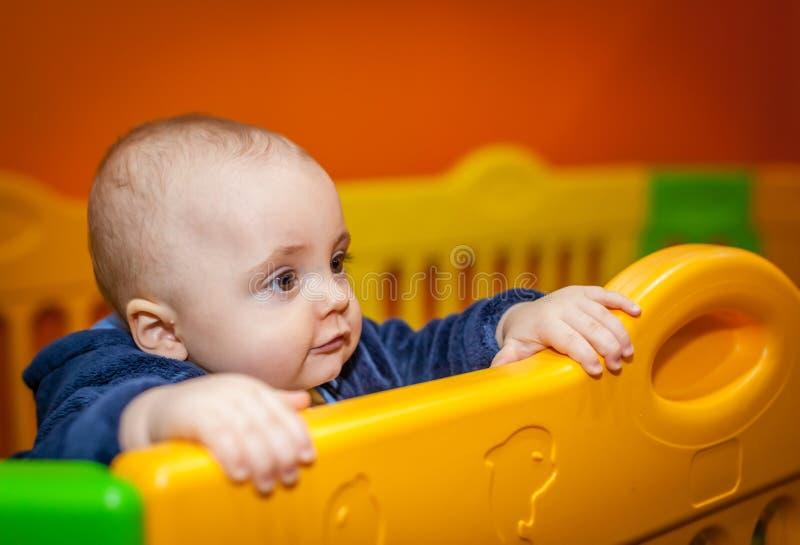 Rapaz pequeno em um campo de jogos interno foto de stock royalty free