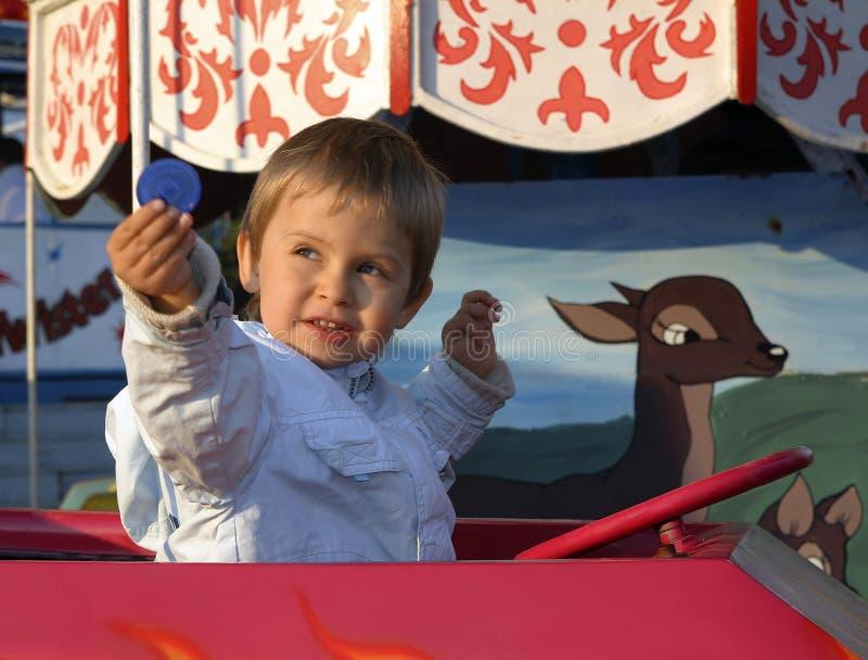 Rapaz pequeno em um merry-go-round foto de stock
