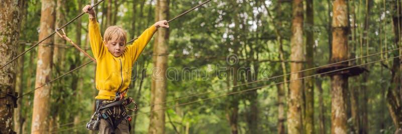 Rapaz pequeno em um parque da corda Recreação física ativa da criança no ar fresco no parque Treinamento para crianças imagens de stock