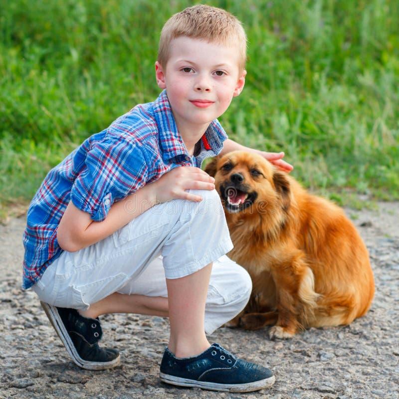 Rapaz pequeno em uma camisa de manta que senta-se na estrada com um cão vermelho foto de stock