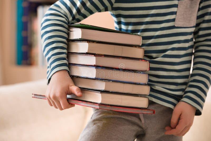 Rapaz pequeno em uma camisa listrada que guarda uma pilha dos livros Conceito da instrução e do conhecimento Crianças da leitura  foto de stock