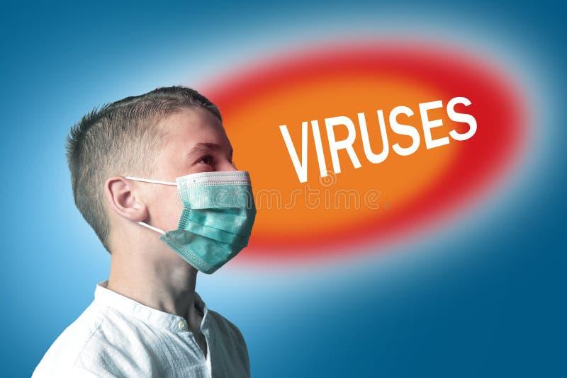 Rapaz pequeno em uma máscara médica em um fundo brilhante com VÍRUS da inscrição foto de stock
