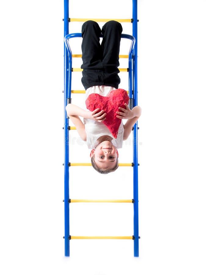 Rapaz pequeno em uma suspensão da camisa de cabeça para baixo na barra e no coração do vermelho das posses fotos de stock