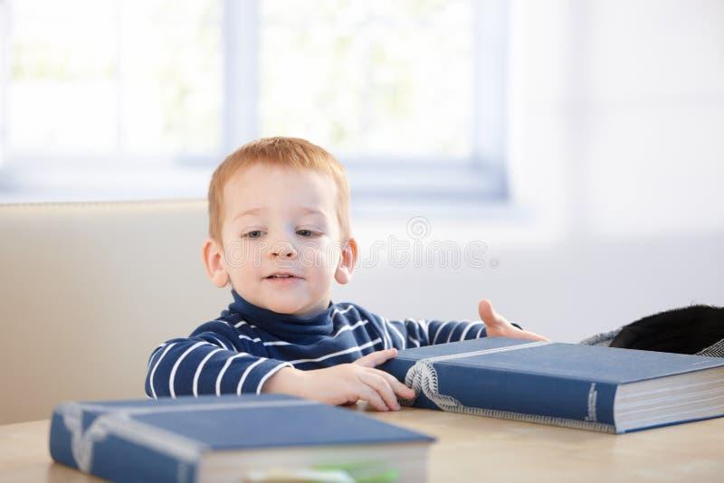 Rapaz pequeno encantador que senta-se na tabela com livros fotos de stock