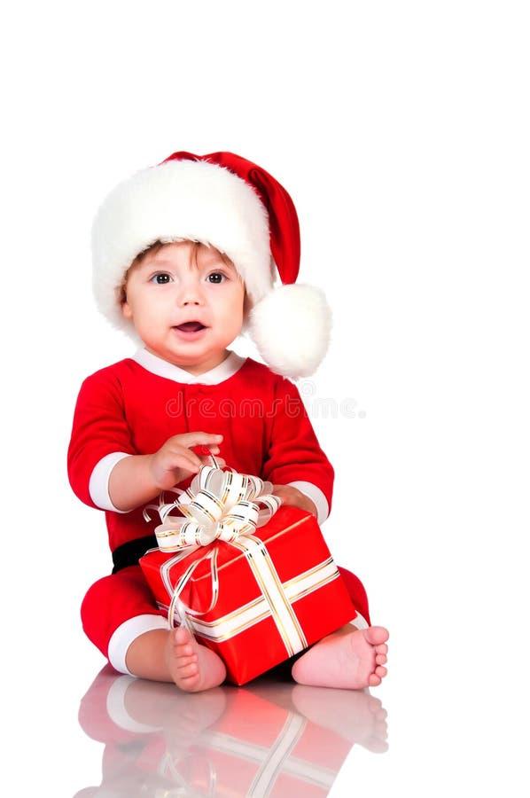 Rapaz pequeno engraçado no terno de Santa Claus com caixas de presente Feriados do ano novo feliz e do Natal fotografia de stock
