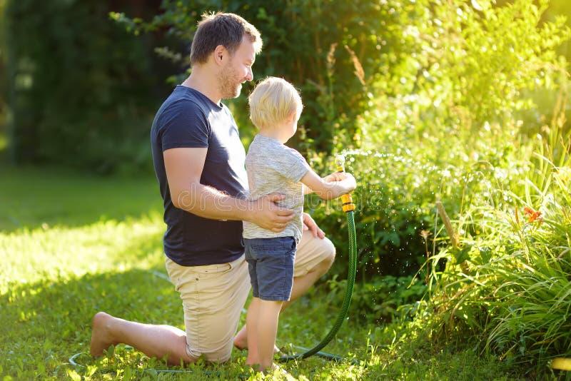 Rapaz pequeno engra?ado com seu pai que joga com a mangueira de jardim no quintal ensolarado Crian?a da crian?a em idade pr?-esco fotografia de stock royalty free