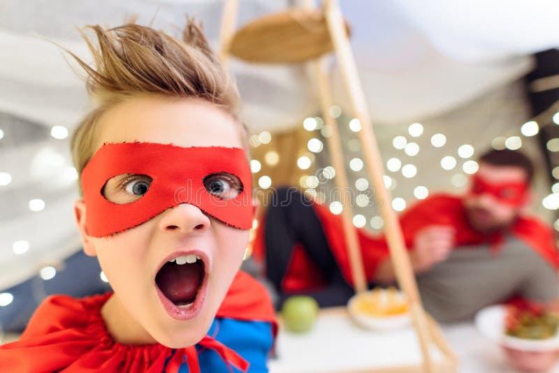 Rapaz pequeno entusiasmado no traje do super-herói que olha a câmera fotografia de stock royalty free