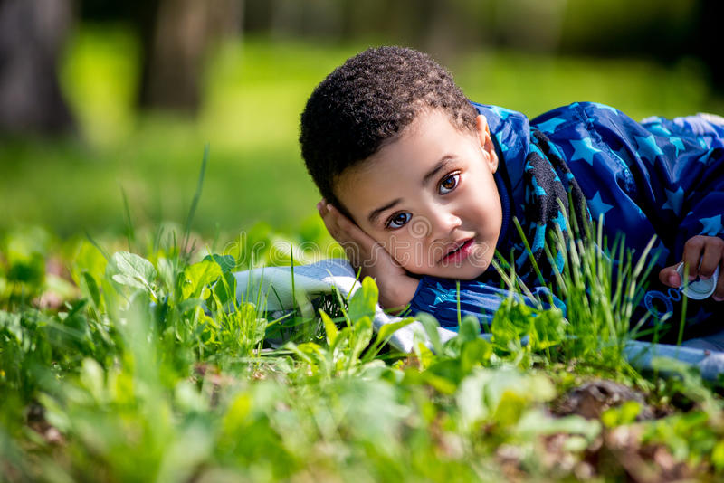 Rapaz pequeno feliz bonito que encontra-se na grama verde na mola imagens de stock royalty free