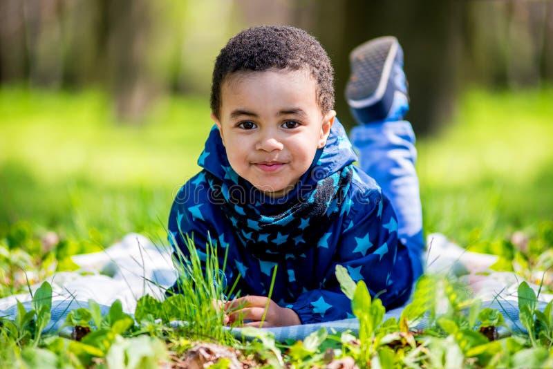 Rapaz pequeno feliz bonito que encontra-se na grama verde na mola foto de stock