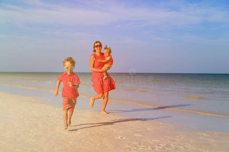 Rapaz pequeno feliz com a mãe e a irmã que correm sobre foto de stock