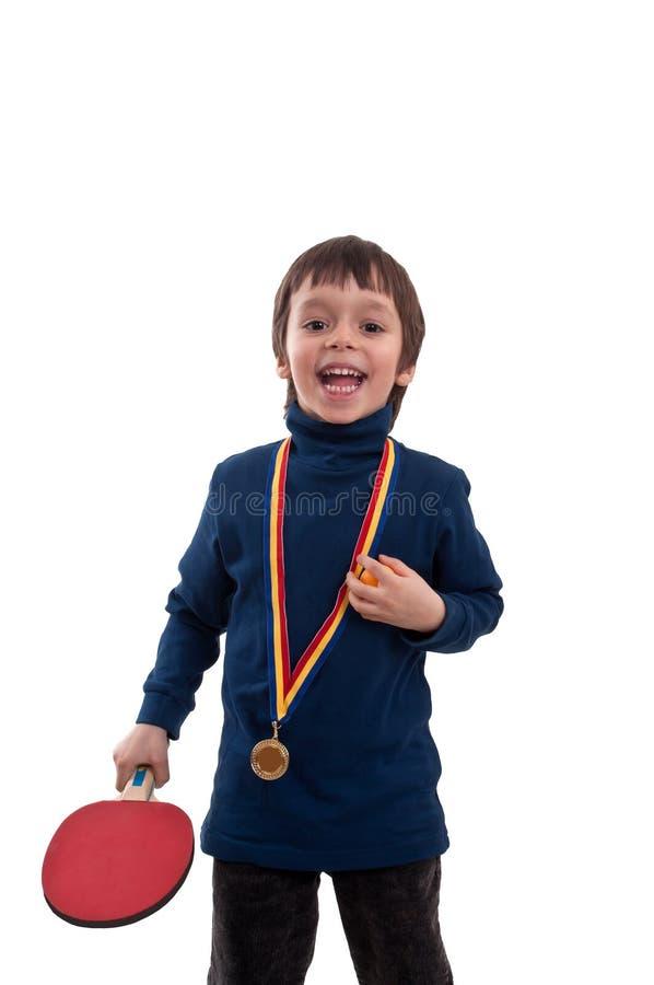 Rapaz pequeno feliz com a medalha de ouro em seus pescoço e raquete de tênis de mesa à disposição imagens de stock