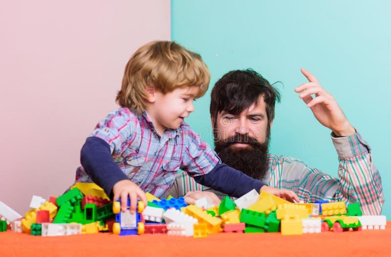rapaz pequeno feliz com o paizinho farpado do homem que joga junto r casa da constru??o com colorido foto de stock