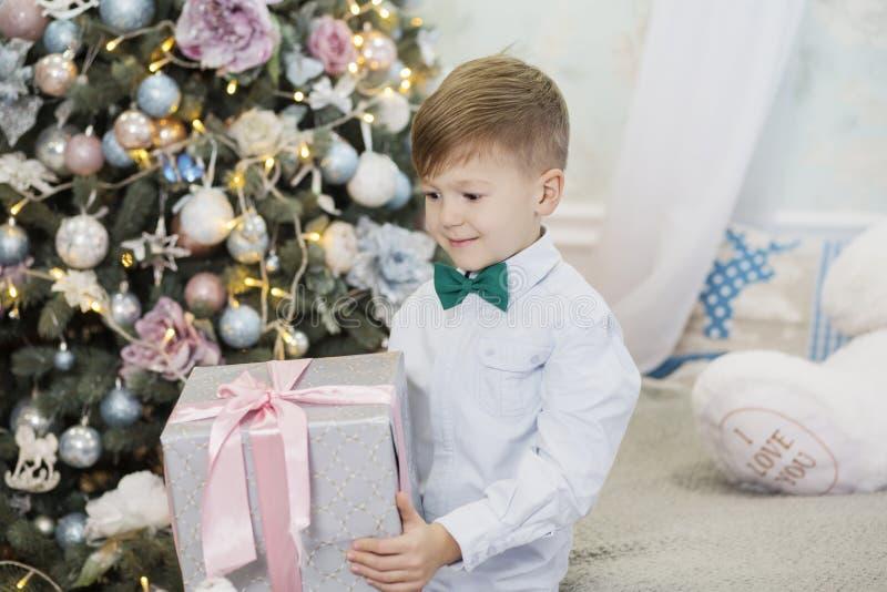 Rapaz pequeno feliz com presente do Natal menino deleitado com presente Crian?a bonito que prepara-se em casa para a celebra??o d imagem de stock
