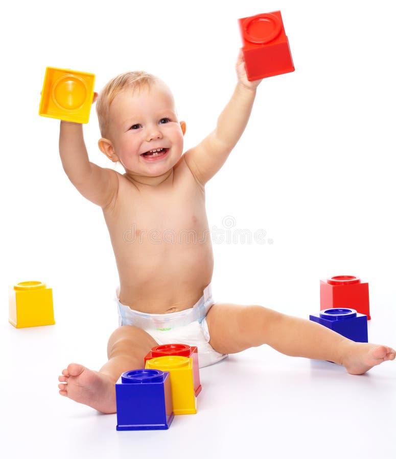 Rapaz pequeno feliz com tijolos do edifício fotos de stock royalty free