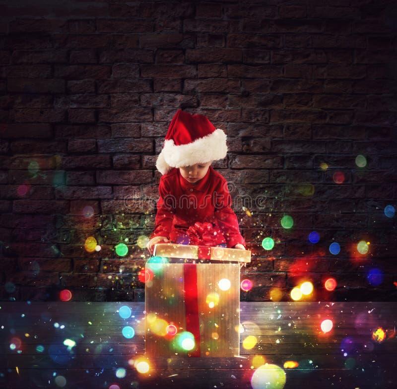 Rapaz pequeno feliz com um presente do Natal fotos de stock