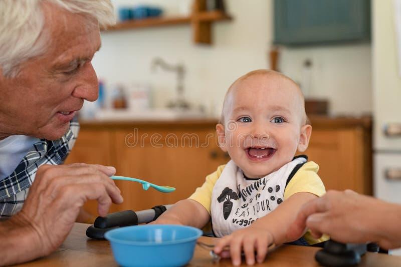 Rapaz pequeno feliz de alimenta??o de primeira gera??o fotografia de stock royalty free