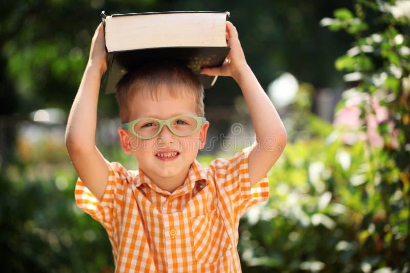 Rapaz pequeno feliz do retrato que guarda um livro grande em seu primeiro dia à escola ou ao berçário Fora, de volta ao conceito  fotografia de stock royalty free