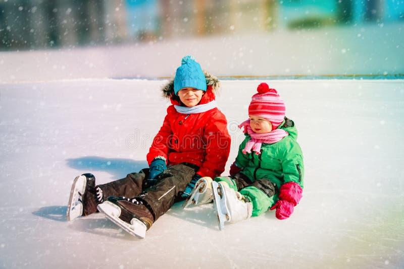Rapaz pequeno feliz e menina que patinam junto foto de stock