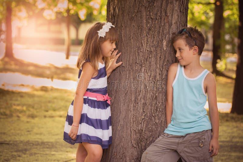 Rapaz pequeno feliz e uma menina que está ao lado de uma árvore na paridade fotografia de stock