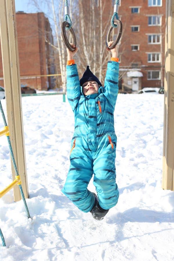 Rapaz pequeno feliz em jogos totais mornos fora no inverno imagem de stock