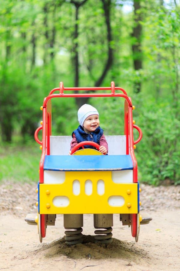 Rapaz pequeno feliz em uma atração das crianças - a máquina que balança no campo de jogos imagens de stock royalty free