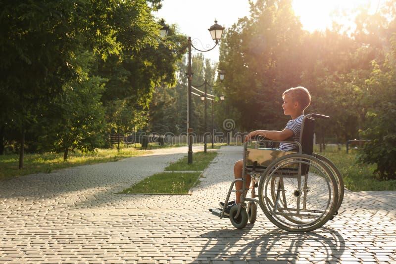 Rapaz pequeno feliz na cadeira de rodas no parque no dia ensolarado espa?o fotos de stock