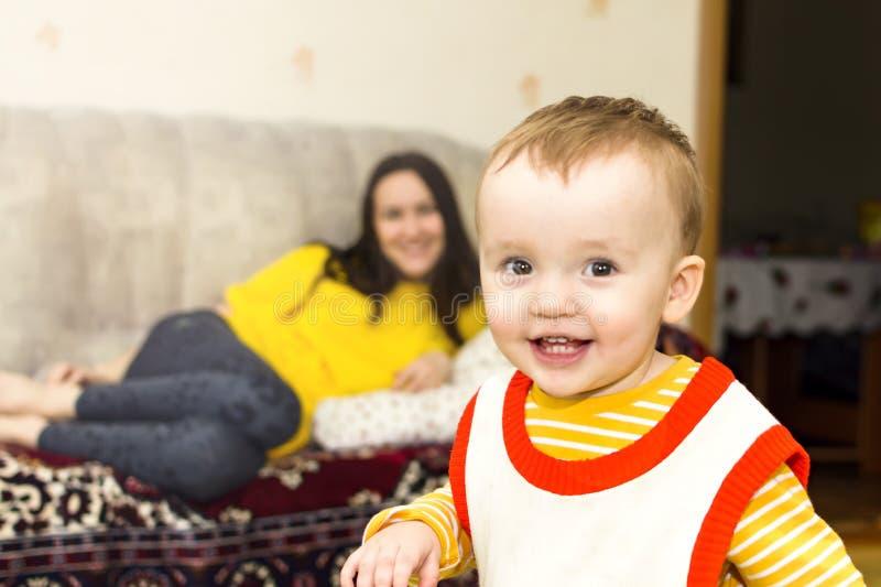 Rapaz pequeno feliz no fundo de sua família do ` s da mãe, apreciando os momentos da felicidade fotos de stock
