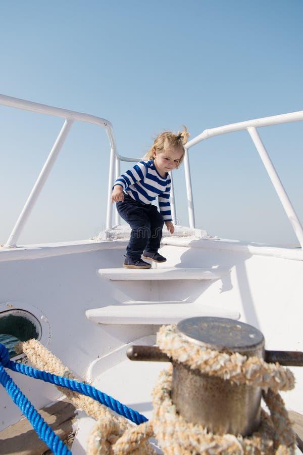 Rapaz pequeno feliz no iate viagem do barco pelo mar ou pelo oceano crian?a engra?ada em camisa marinha listrada viagem e desejo  foto de stock royalty free