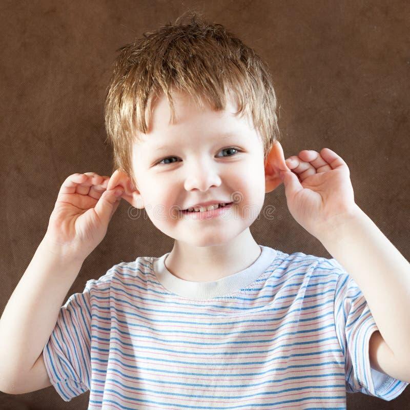 Rapaz pequeno feliz, puxando as orelhas imagens de stock royalty free