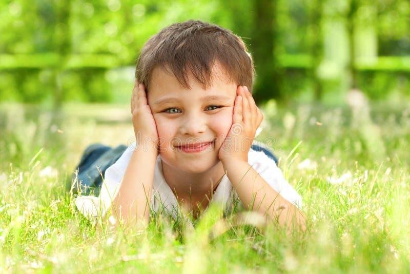 Rapaz pequeno feliz que coloca na grama foto de stock royalty free
