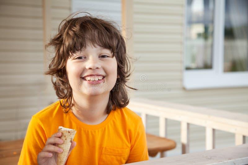 Rapaz pequeno feliz que come um gelado imagens de stock
