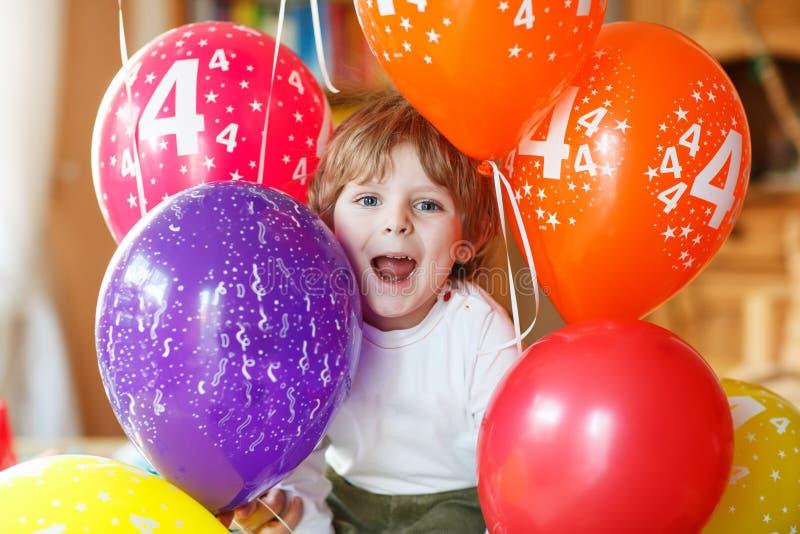 Rapaz pequeno feliz que comemora o seu aniversário 4 com balloo colorido fotografia de stock royalty free
