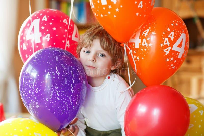 Rapaz pequeno feliz que comemora o seu aniversário 4 com balloo colorido foto de stock
