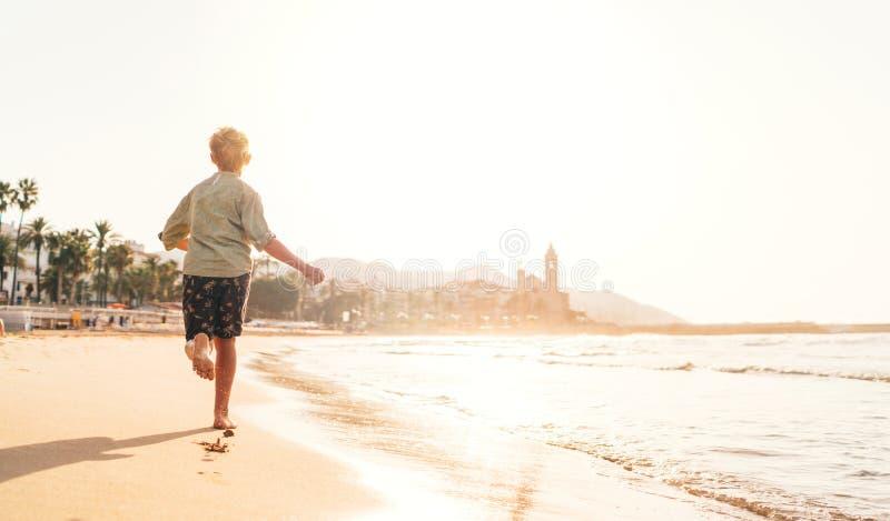 Rapaz pequeno feliz que corre pela costa mediterrânea de spain na cidade de Sitges perto de Barcelona imagem de stock