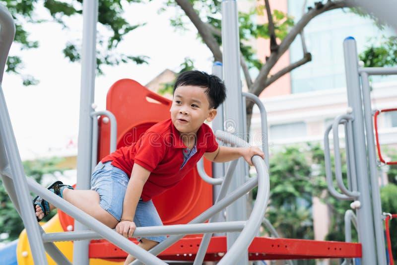 Rapaz pequeno feliz que escala no campo de jogos das crianças foto de stock