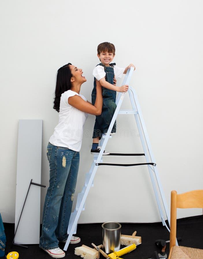 Rapaz pequeno feliz que escala uma escada imagens de stock royalty free